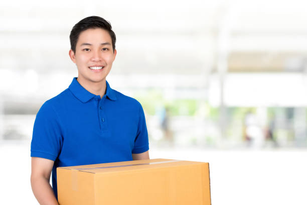 Friendly Asian delivery man  in blue polo shirt carrying parcel box Handsome friendly smiling Asian delivery man in blue polo shirt carrying parcel box asian handsome man stock pictures, royalty-free photos & images