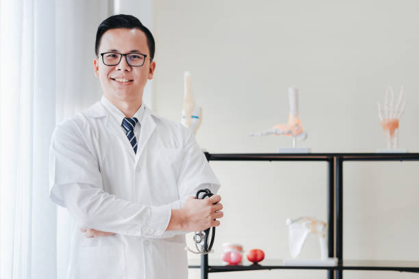 Friendly Asian doctor holding stethoscope in hand in his office stock photo