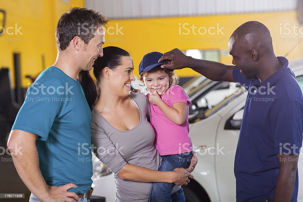 friendly auto mechanic playing with little girl royalty-free stock photo