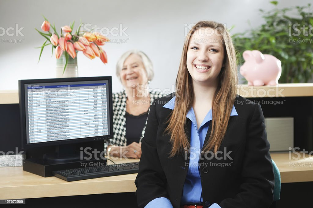 A young Caucasian bank teller in front of the work station of a bank...