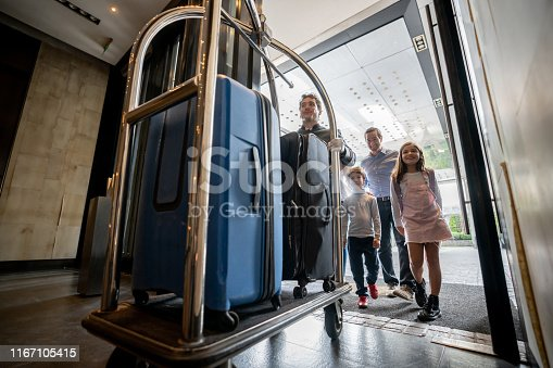 Friendly bellhop pushing cart with guest family luggage on cart ready to check in into hotel - Hotel concepts