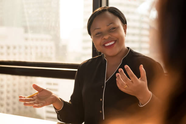 Friendly black businesswoman leader discussing work at the meeting Friendly black businesswoman leader discussing work with colleague at the meeting in office storytelling stock pictures, royalty-free photos & images