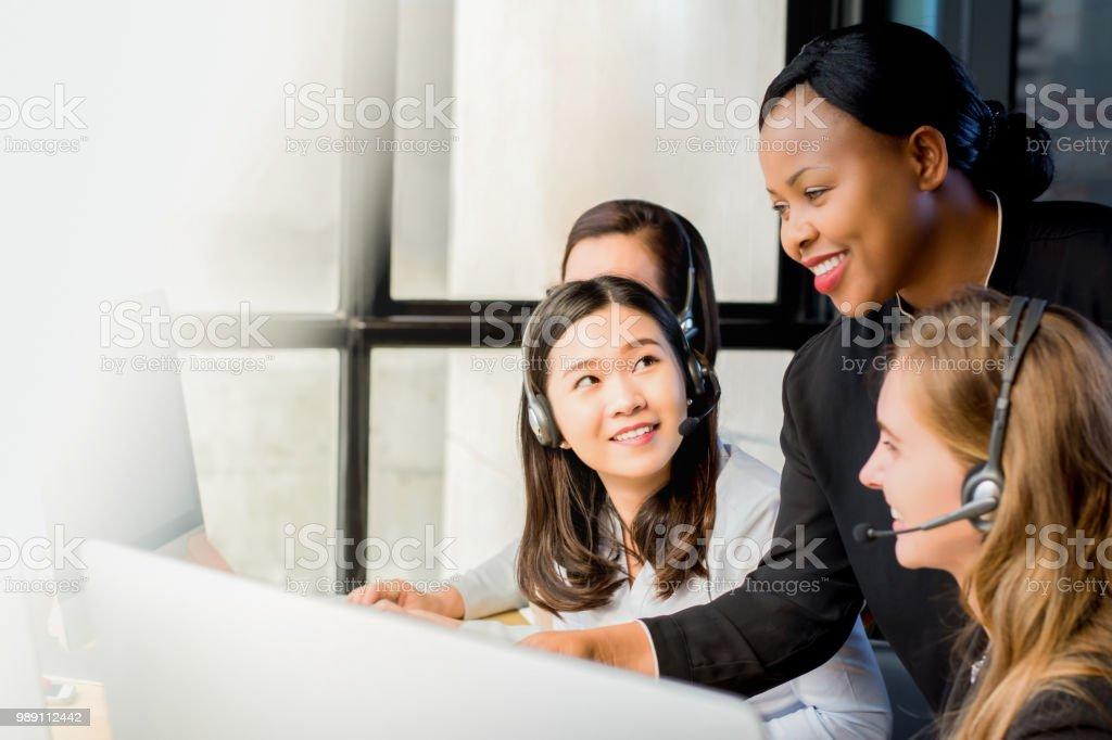 Freundlichen schwarzen geschäftsfrau Betreuer arbeiten mit ihrem Team im Call-center – Foto