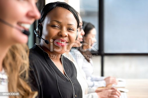 istock Friendly black woman wearing microphone headset working in call center 989800648