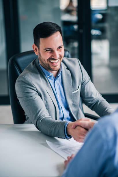 Friendly business handshake. Smiling handsome elegant man handshaking with employee. stock photo