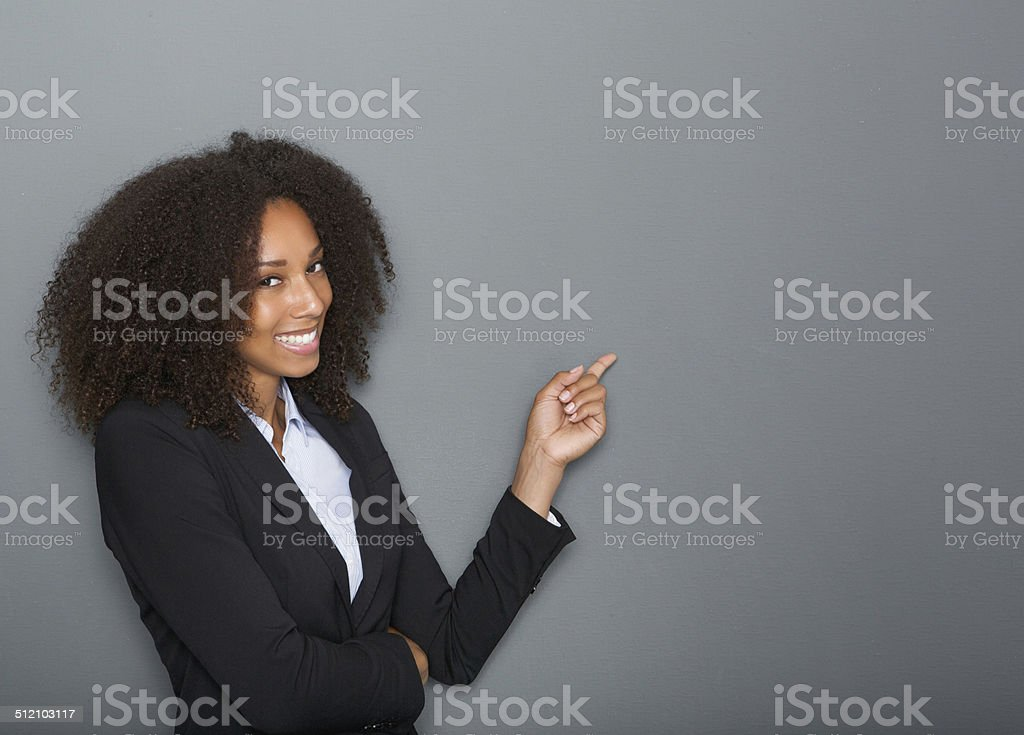 Friendly business woman pointing finger stock photo