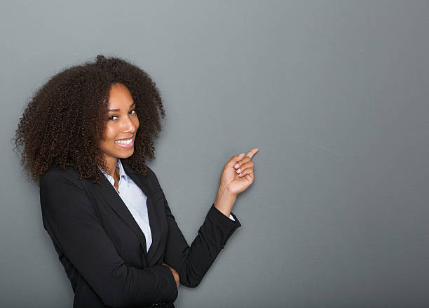 Friendly business woman pointing finger Close up portrait of a friendly business woman pointing finger on gray background presenter stock pictures, royalty-free photos & images