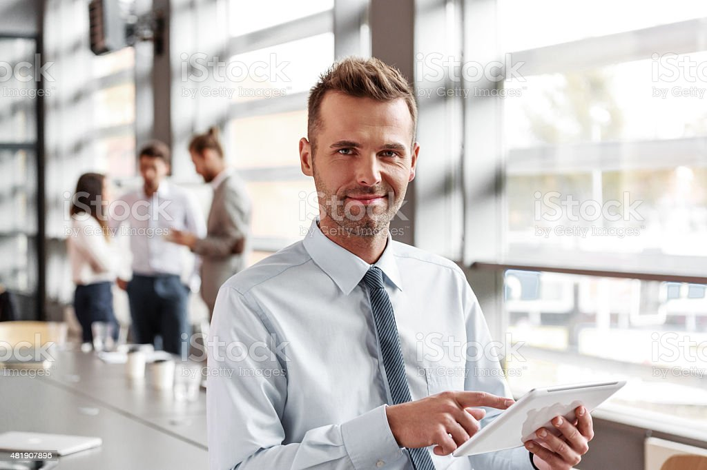 Friendly businessman using a digital tablet in the office Portrait of friendly businessman wearing shirt and tie sitting in the board room, holding a digital tablet in hand and smiling at camera. Coworkers in the background. 2015 Stock Photo