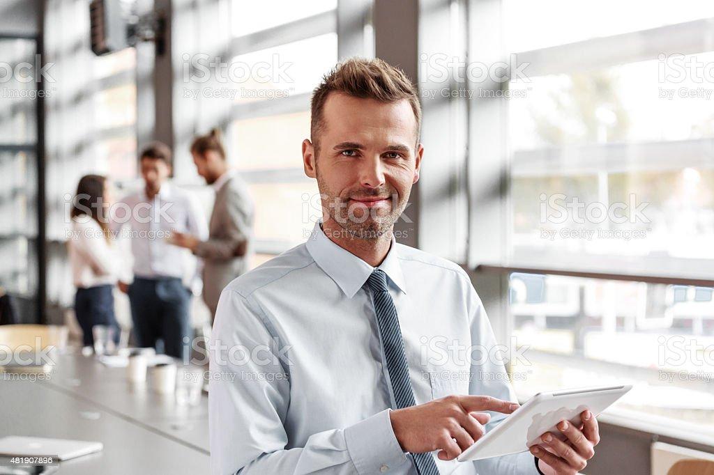 Un uomo d'affari utilizzando una tavoletta digitale in ufficio - foto stock