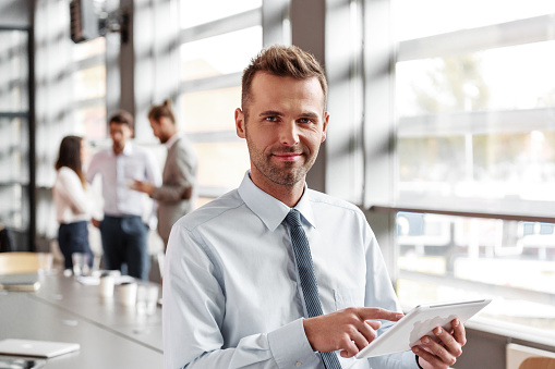 Friendly Businessman Using A Digital Tablet In The Office Stock Photo - Download Image Now