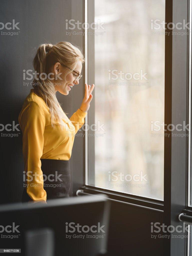 Friendly businesswoman greeting friend though glass window stock photo