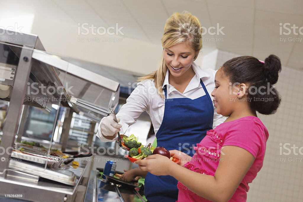 Friendly cafeteria worker serving lunch to student in school stock photo