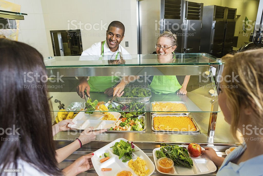 Friendly cafeteria workers serving healthy food to high school students stock photo