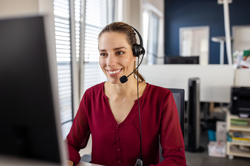 Shot of a friendly young call center agent sitting at her desk. Businesswoman wearing headset and using computer while working in call center.