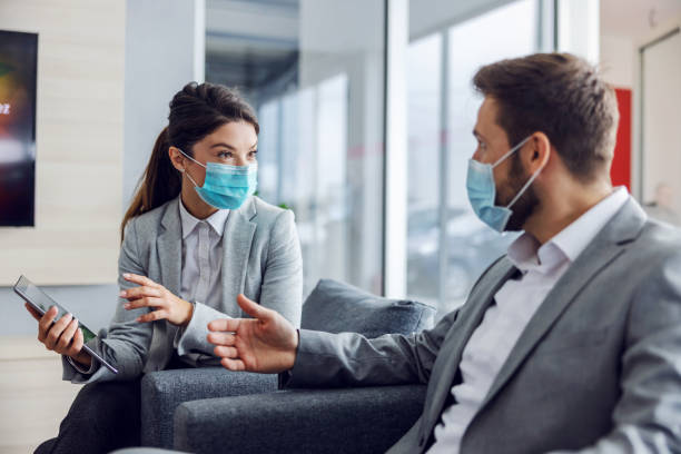 Friendly car seller with face mask sitting with customer in car salon, holding tablet and talking about specifications and performances of car during corona virus. stock photo