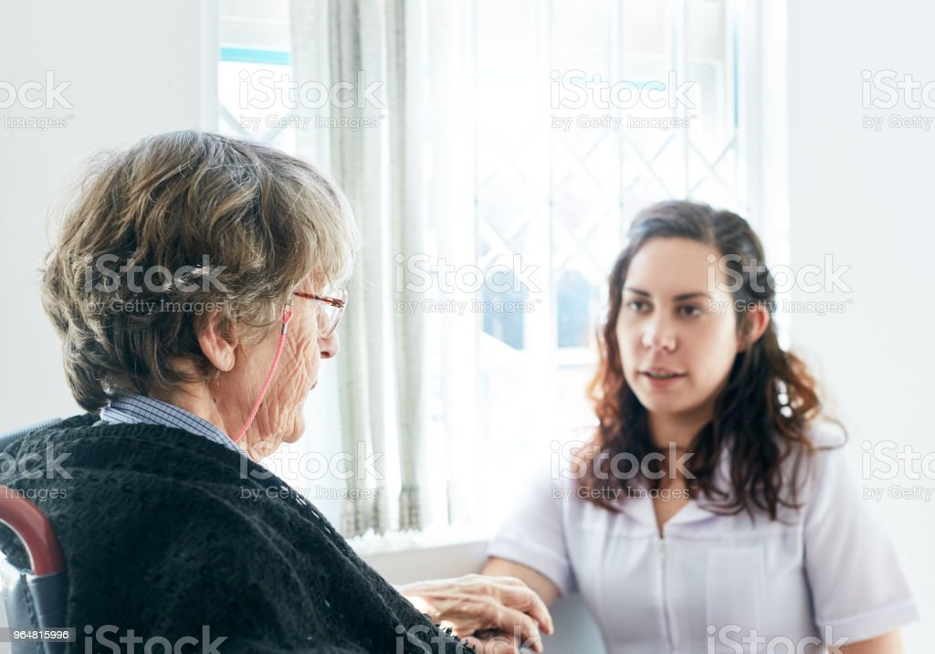 Friendly caregiver chats to her senior woman patient royalty-free stock photo