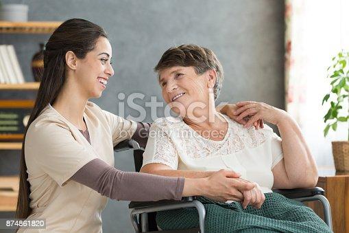 istock Friendly caregiver woman hugging senior 874861820