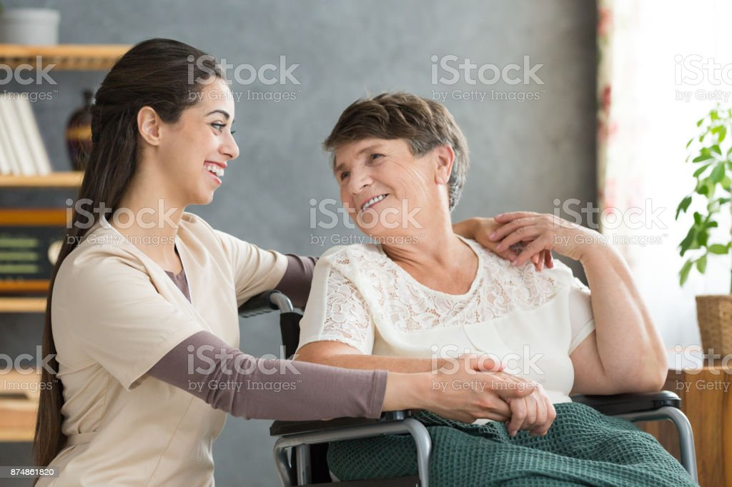 Friendly caregiver woman hugging senior stock photo