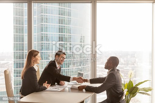 istock Friendly caucasian employers and african-american applicant handshaking, welcoming at interview 695760158