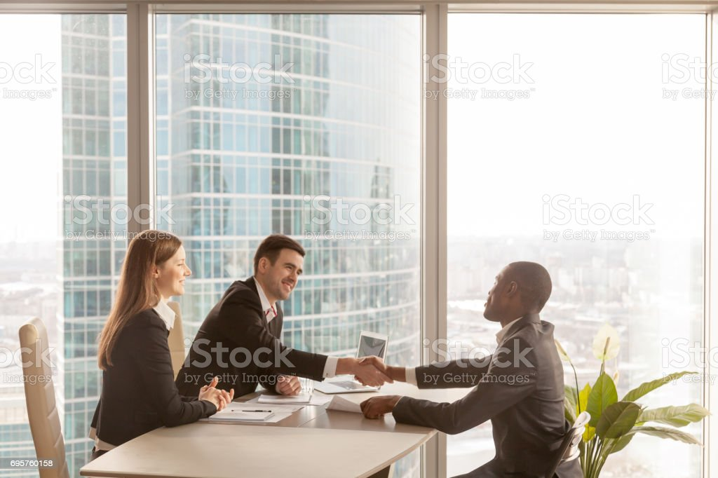Friendly caucasian employers and african-american applicant handshaking, welcoming at interview stock photo