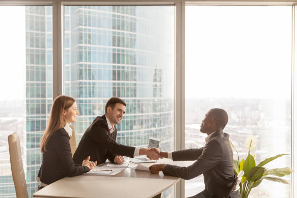 friendly caucasian employers and african-american applicant handshaking, welcoming at interview - job interview stock pictures, royalty-free photos & images