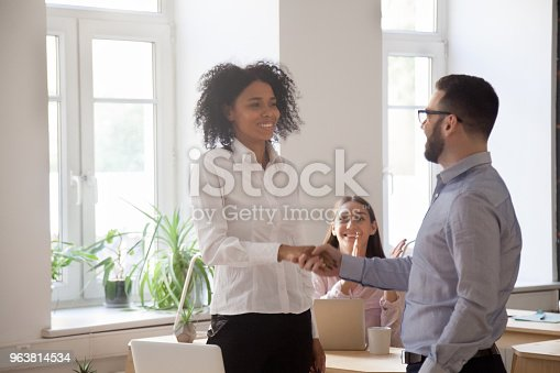 923041456 istock photo Friendly ceo promoting rewarding congratulating handshaking successful female african employee 963814534
