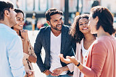 Multi-ethnic group of smiling young people talking outdoors in the city
