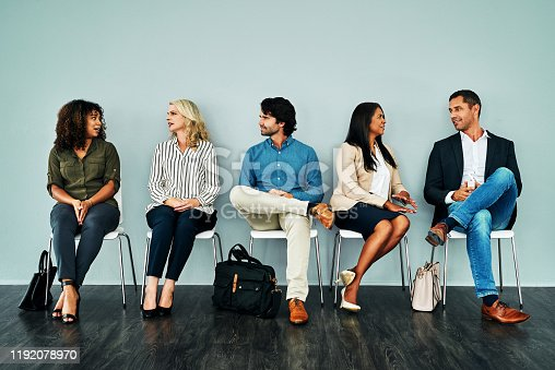 Studio shot of a group of businesspeople having a conversation while waiting together against a blue background