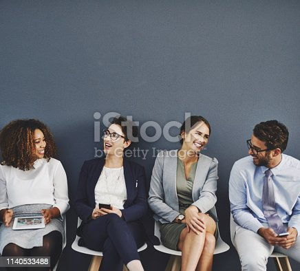Studio shot of a group of businesspeople talking while waiting in line against a gray background