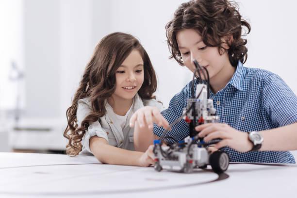 freundliche kinder bei der nutzung moderner technologien in der schule - lernfortschrittskontrolle stock-fotos und bilder