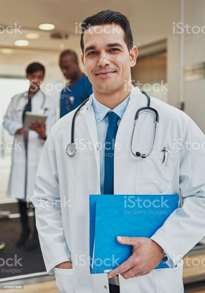 Friendly confident Hispanic doctor stock photo