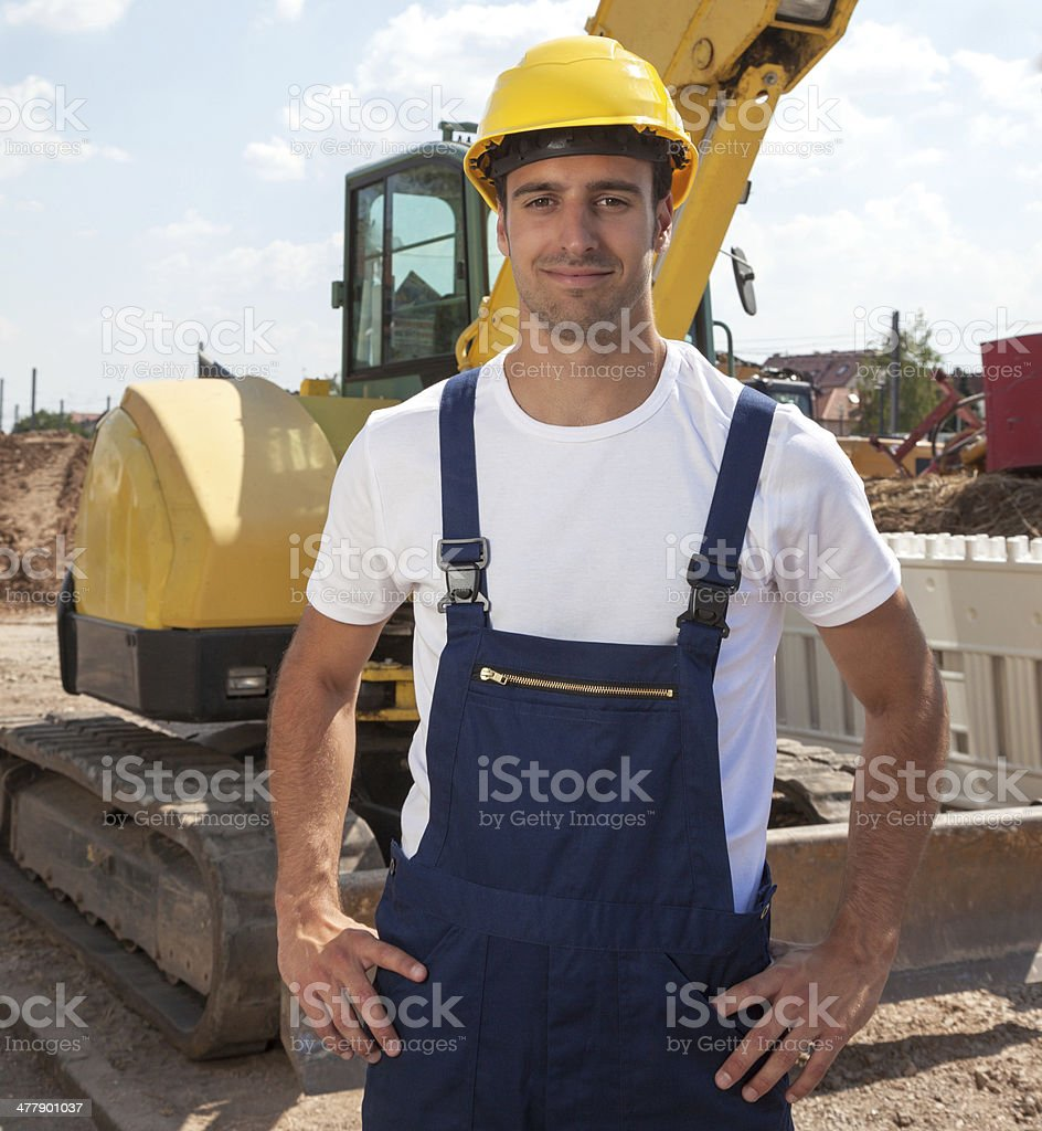 Friendly construction worker in front of his excavator royalty-free stock photo