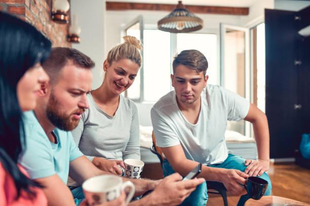 parejas amigables navegando en las redes sociales mientras disfruta de la recolección de café - happy couple sharing a cup of coffee fotografías e imágenes de stock