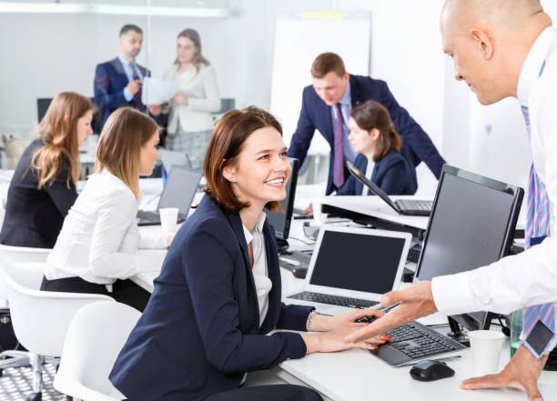 Colegas de trabalho amigáveis, tendo agradável diversão conversa no local de trabalho no escritório moderno - foto de acervo