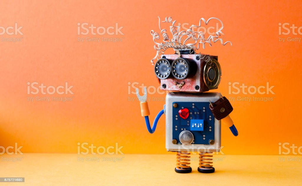 Friendly crazy robot handyman on orange background. Creative design cyborg toy. Copy space photo stock photo