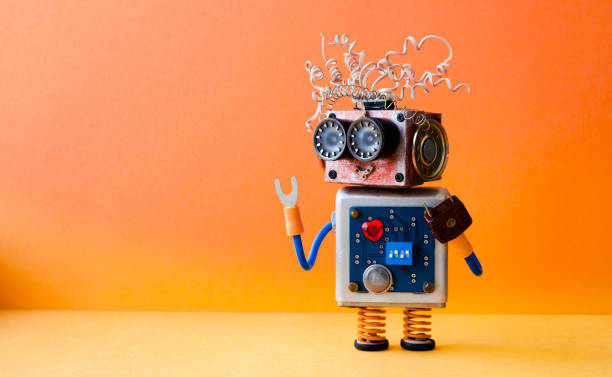friendly crazy robot handyman on orange background. creative design cyborg toy. copy space photo - cybernetic stock pictures, royalty-free photos & images
