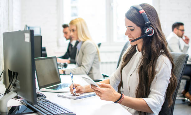 Friendly customer support female operator with headphones writing notes to notebook taken from smartphone at office stock photo