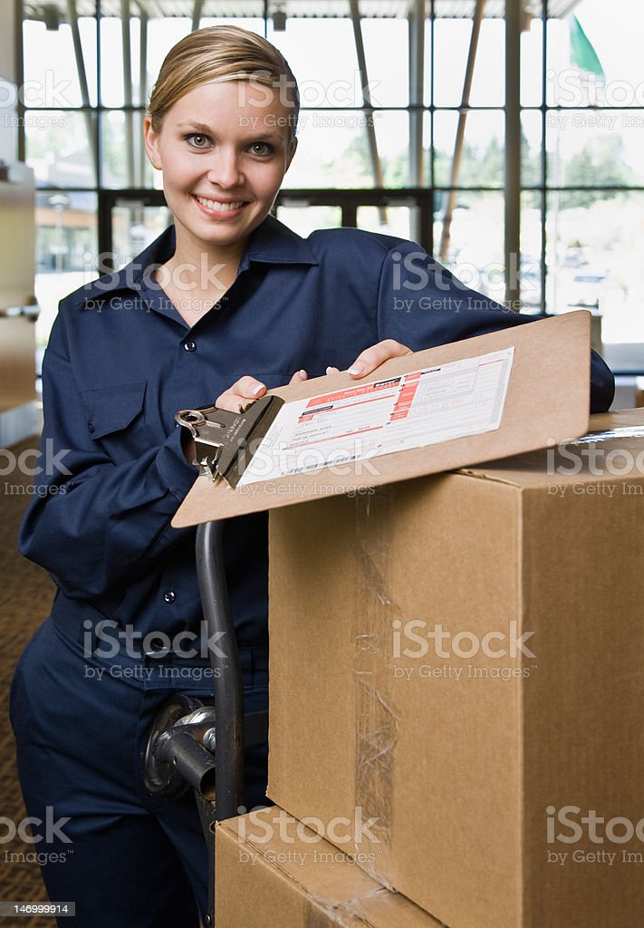 Friendly delivery woman in uniform with stack of cardboard boxes royalty-free stock photo