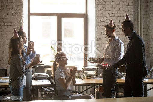 istock Friendly diverse employees congratulating happy woman colleague with birthday 1085714024