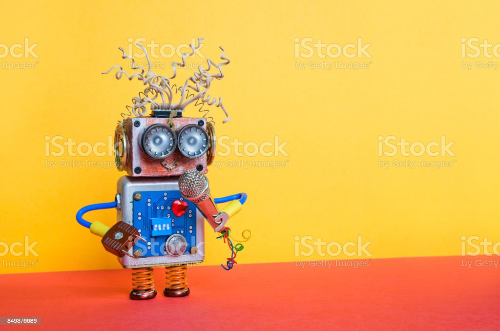 Friendly entertainer robot with microphone. Music lecture performance poster design. Smiley face cyborg toy, yellow wall red ground decoration background stock photo