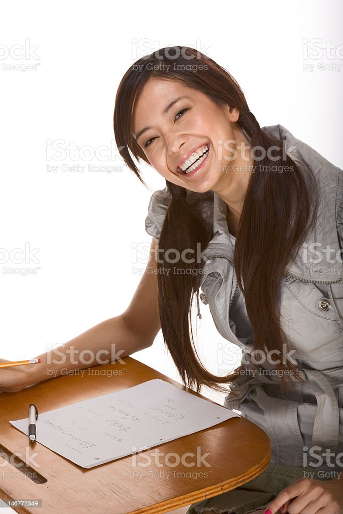 Friendly excited Asian college student by desk royalty-free stock photo