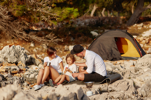 Friendly family, sitting near tent on stone seacoast at daytime