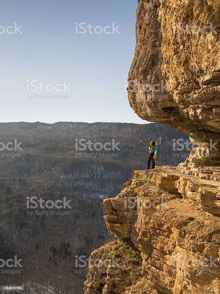 Friendly family standing on a rock stock photo