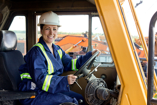 A royalty free image from the oil or construction industry of a friendly female worker driving a dump truck.