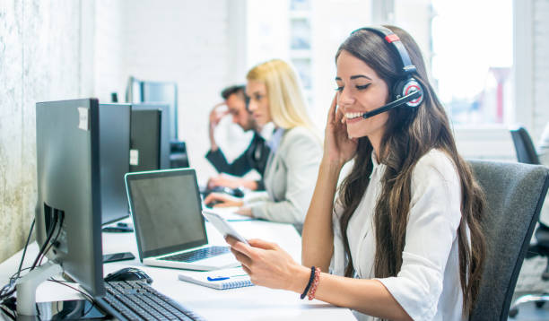 Friendly female customer support operator with headset using phone in office stock photo