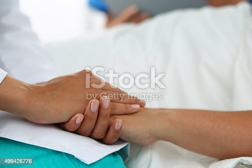 istock Friendly female doctor hands holding patient hand 499426776