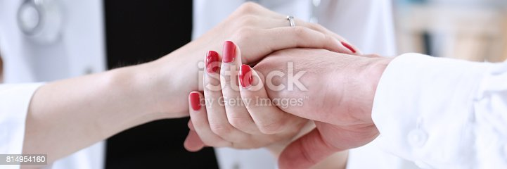 1133353454istockphoto Friendly female doctor hold male patient hand in office 814954160