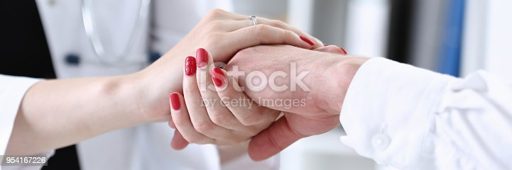 1133353454istockphoto Friendly female doctor hold male patient hand 954167226
