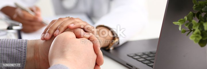 1133353454istockphoto Friendly female doctor hold male patient 1050392172