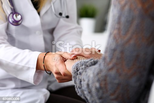 istock Friendly female doctor hold patient hand in office during recept 639863006